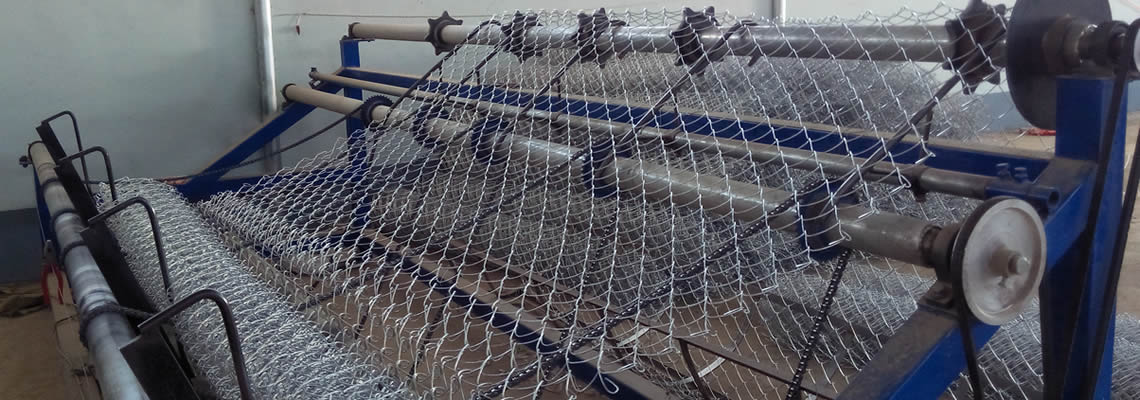 A blue chain link fence machine is producing galvanised chain link fence.