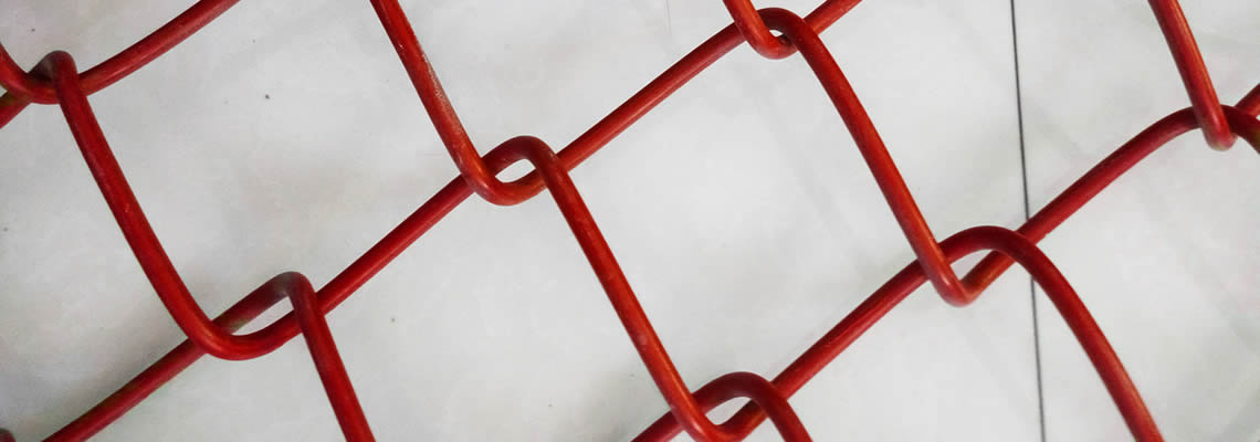 A red coated chain link fence panel