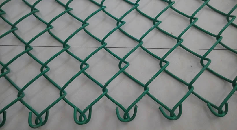 Green PVC coated chain link fence panel with knuckled top on the ground.