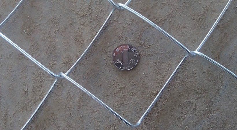 Galvanised chain link mesh on the ground and one yuan coin in the mesh hole.