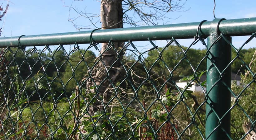 Green PVC coating chain link fencing protects grass land.