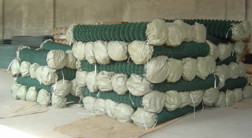 Many green PVC coated chain link fence rolls in our factory warehouse.