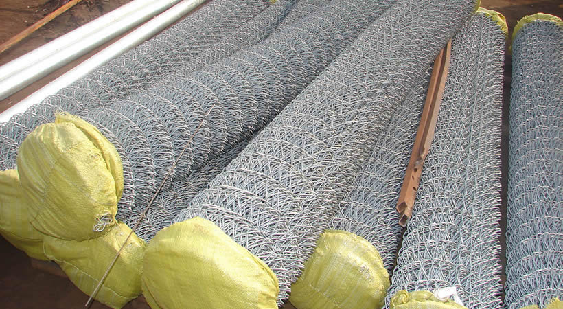 Many galvanized chain link mesh rolls ends  wrapped up with yellow plastic woven bags.