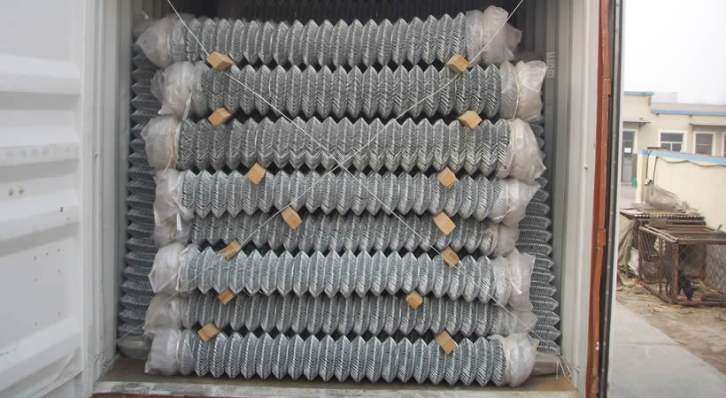Galvanized chain link mesh rolls loaded in container, with wooden stick.