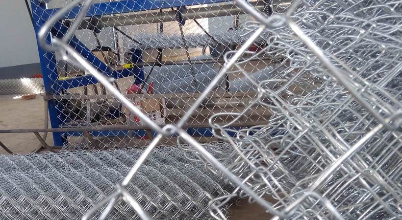 Many galvanized chain link mesh rolls and panels, the background is chain link machine in workshop.