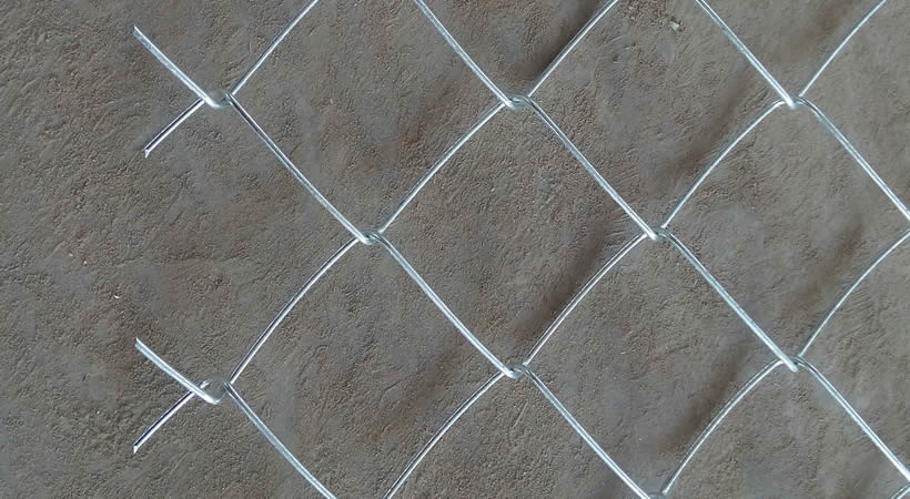 A galvanised chain link mesh with barbed edge on the ground.