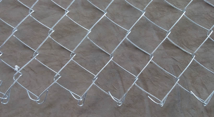 A galvanised chain link mesh with knuckled edge on the ground.