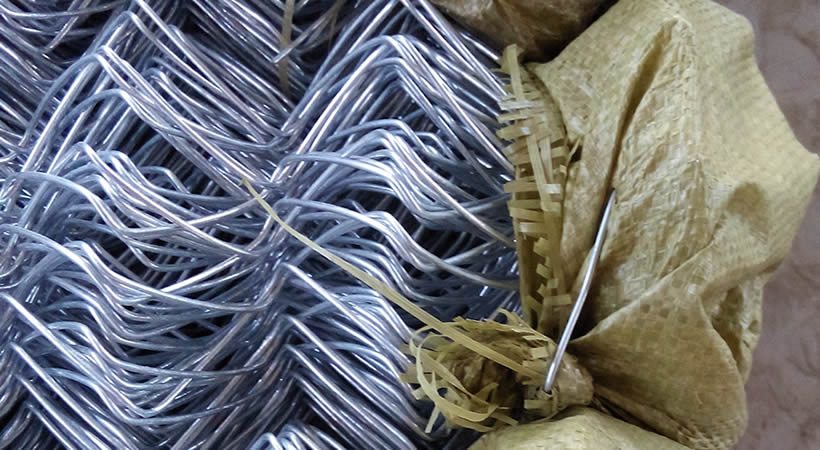 Three rolls of galvanized chain link fence ends wrapped with woven bags.