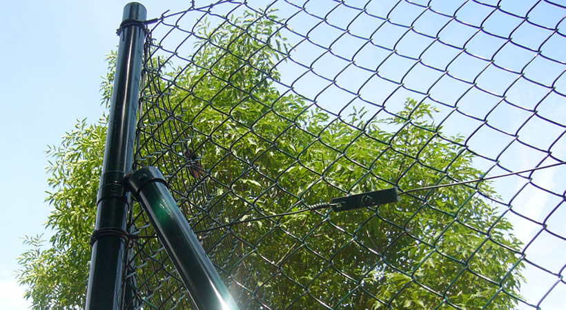 A high chain link fence installed with green posts and wire tension clamps.