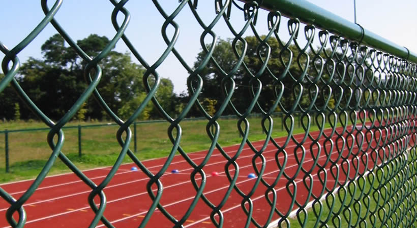 Green PVC coated chain link fence for sports fencing.